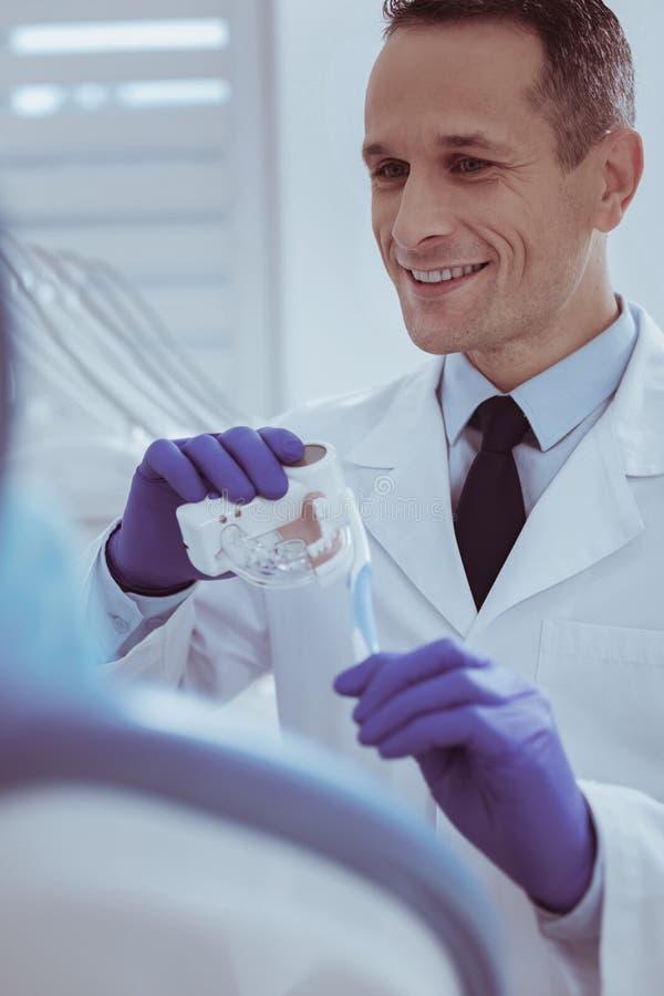 Tamaño calculador de las dentaduras del dentista de sexo masculino adorable fotografía de archivo libre de regalías