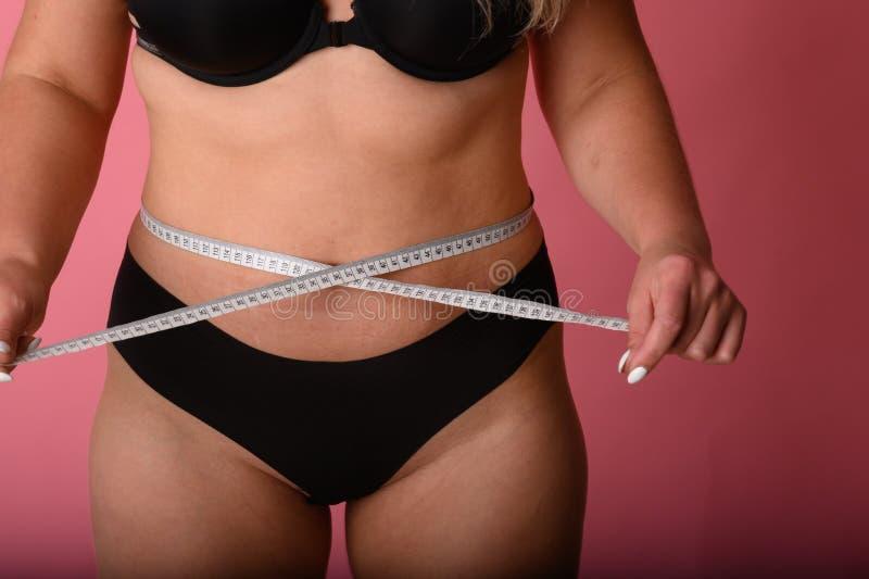 Tamaño más muchacha con la cinta métrica alrededor del positivo del cuerpo de la cintura imagen de archivo libre de regalías