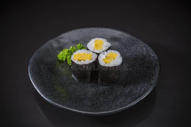 Tamago Maki sirvió en plato de cerámica japonés tradicional foto de archivo libre de regalías