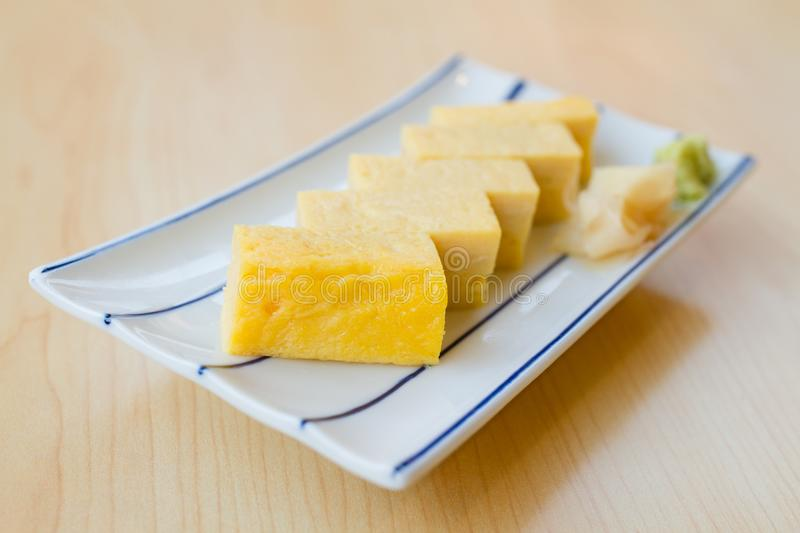 TAMAGOYAKI or Japanese Sweet Egg. Close up TAMAGOYAKI or Japanese Sweet Egg with wasabi and Pickled ginger on white plate on wooden table stock photography
