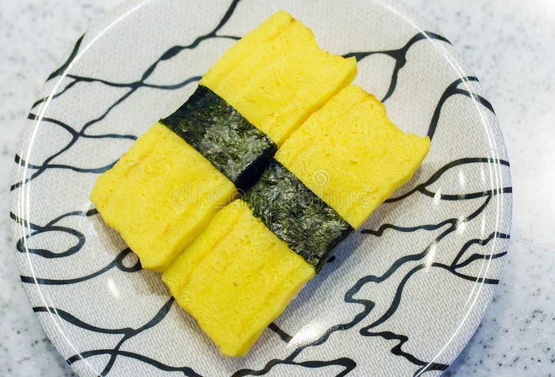 Tamagoyaki sushi eller söt omelett med ris i platta Tamagoyaki royaltyfria bilder