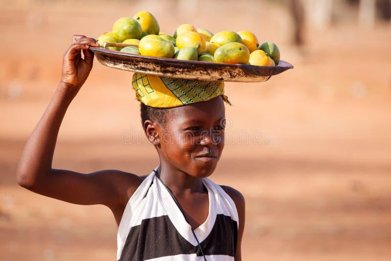 TAMALE, στις 22 Μαρτίου ¿ ½ της ΓΚΑΝΑΣ ï: Το μη αναγνωρισμένο νέο αφρικανικό κορίτσι φέρνει στοκ φωτογραφία με δικαίωμα ελεύθερης χρήσης