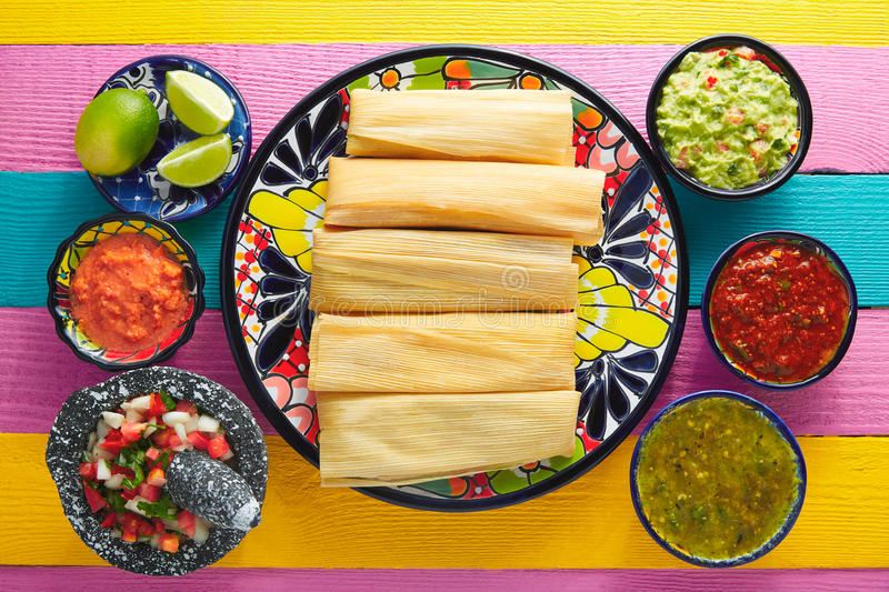 Tamale with corn leaf and sauces guacamole stock photos