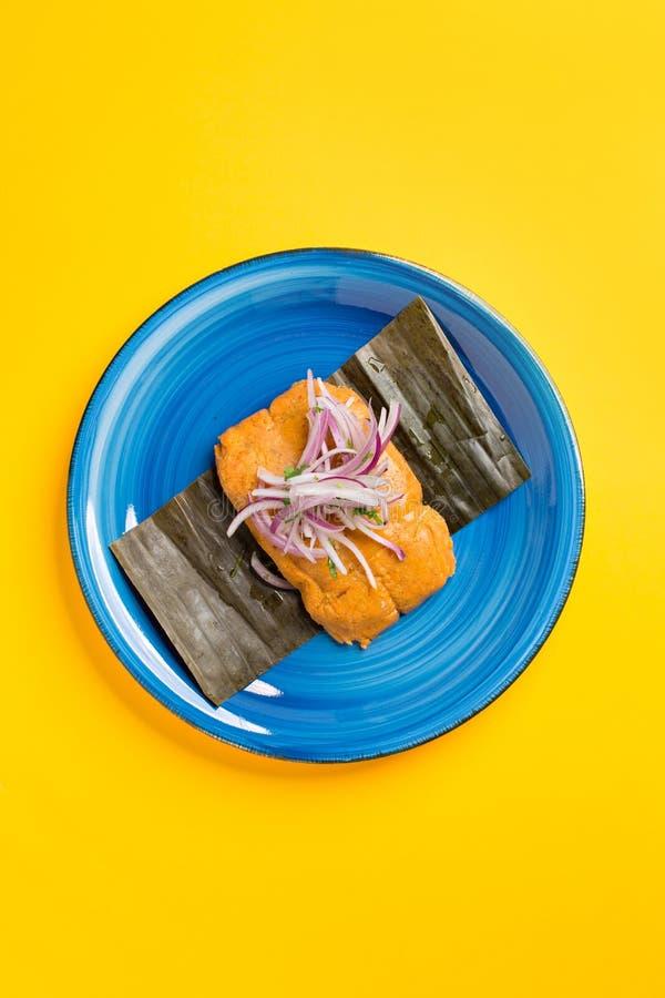 Tamale peruano, café da manhã peruano típico feito do milho e enchido com galinha e servido com salada da cebola roxa fotografia de stock