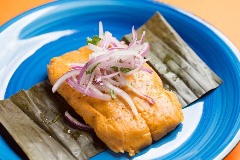 Tamale peruano, café da manhã peruano típico feito do milho e enchido com galinha e servido com salada da cebola roxa fotos de stock