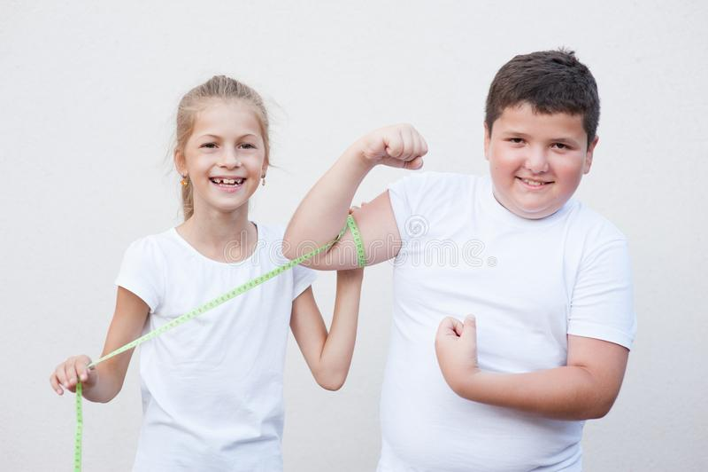Tamanho gordo grande de sorriso de medição do músculo do menino da menina pequena magro bonita pela fita fotos de stock