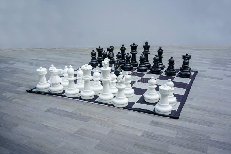 Tamanho grande super das partes preto e branco do jogo de xadrez, figuras na placa de xadrez fotos de stock