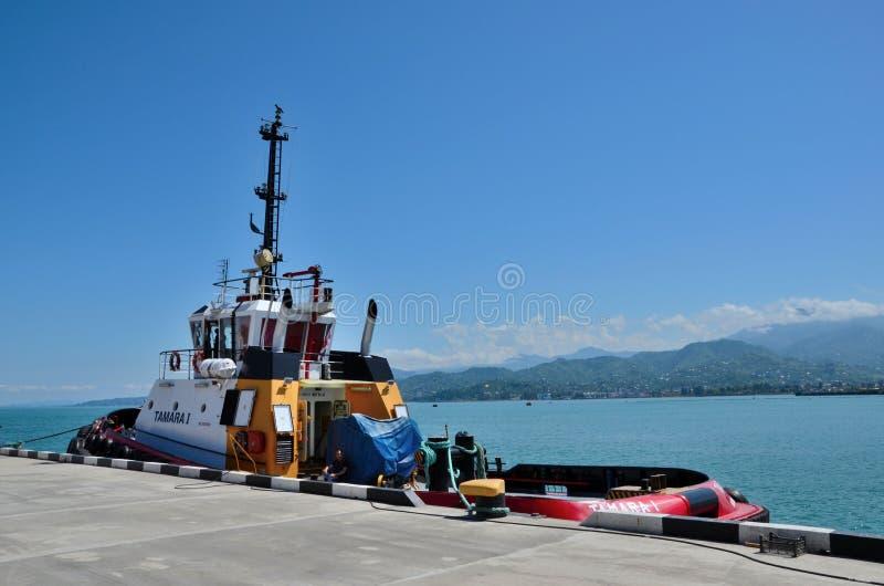Tamarai-Schlepper angekoppelt auf Küstenhafen mit Mannschaftsmitgliedern innerhalb Port-Batumis Georgia lizenzfreie stockfotografie