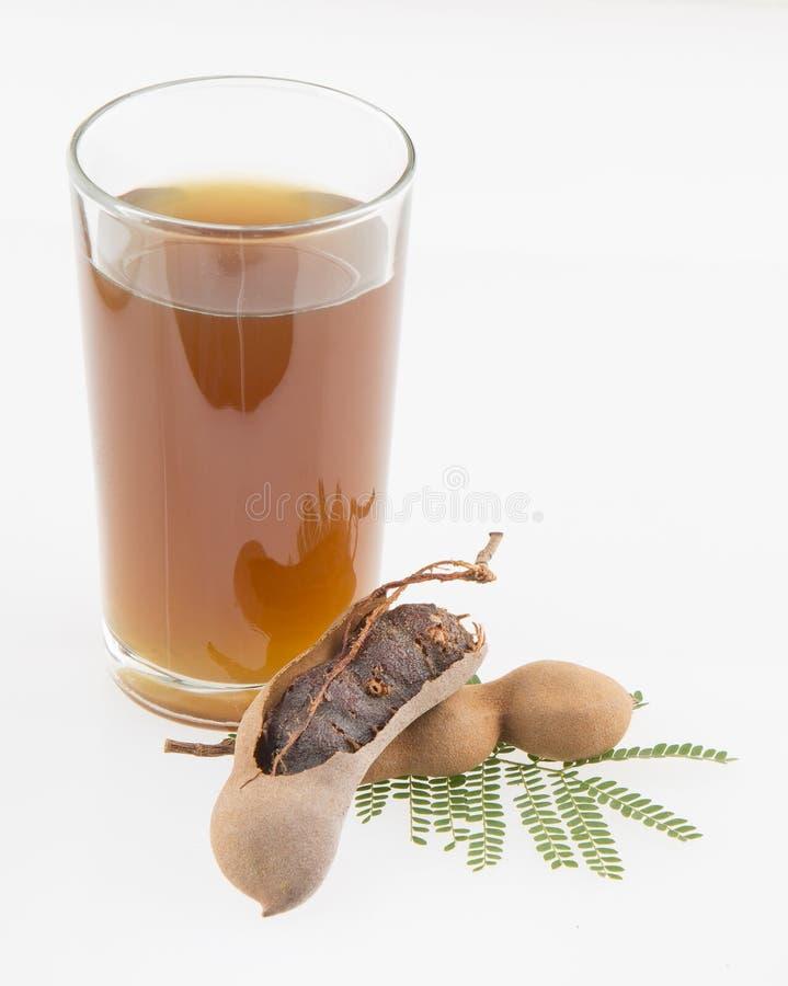 Tamarindensaft in einem Glas umgab durch frische reife Tamarinden - Tamarindus indica Weißer Hintergrund lizenzfreie stockfotos