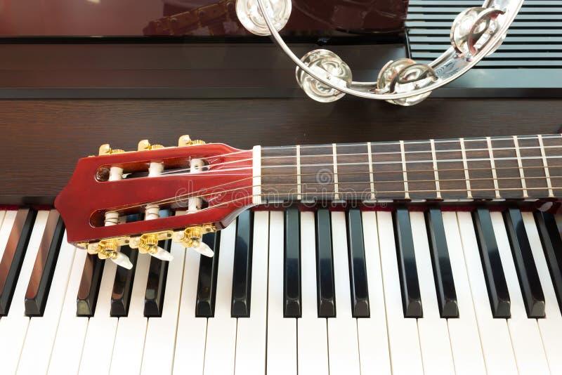 Tamboerijn en hals van gitaar op pianotoetsenbord stock fotografie