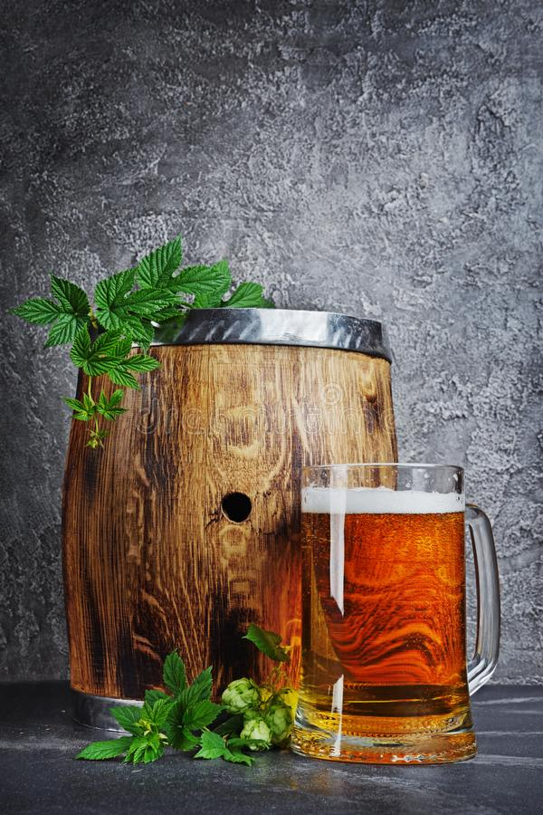 Tambor de madeira da cerveja do ofício com caneca e os lúpulos de vidro na adega escura fotografia de stock royalty free