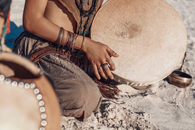 Tambor del chamán en mano de la mujer jugar música étnica imagenes de archivo