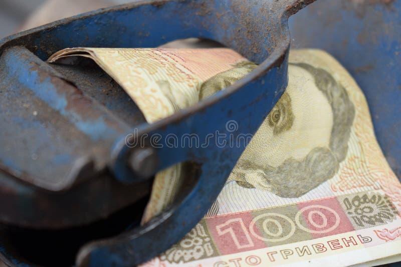 Tambor do metal e dinheiro ucraniano, o conceito do custo da gasolina, diesel, gás Reenchendo o carro Hryvnia da cédula 100 foto de stock royalty free