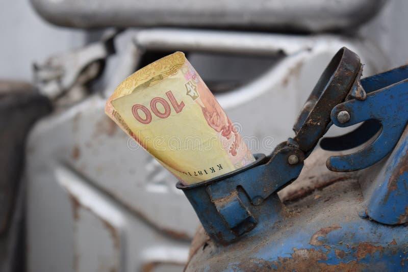 Tambor do metal e dinheiro ucraniano, o conceito do custo da gasolina, diesel, gás Reenchendo o carro Hryvnia da cédula 100 foto de stock