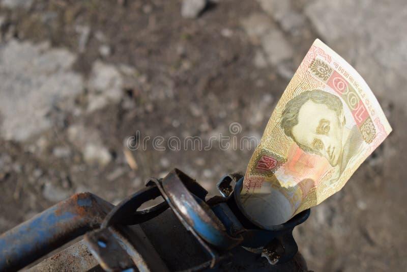Tambor do metal e dinheiro ucraniano, o conceito do custo da gasolina, diesel, gás Reenchendo o carro Hryvnia da cédula 100 imagens de stock