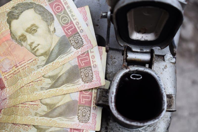 Tambor do metal e dinheiro ucraniano, o conceito do custo da gasolina, diesel, gás Reenchendo o carro Hryvnia das cédulas 100 fotografia de stock