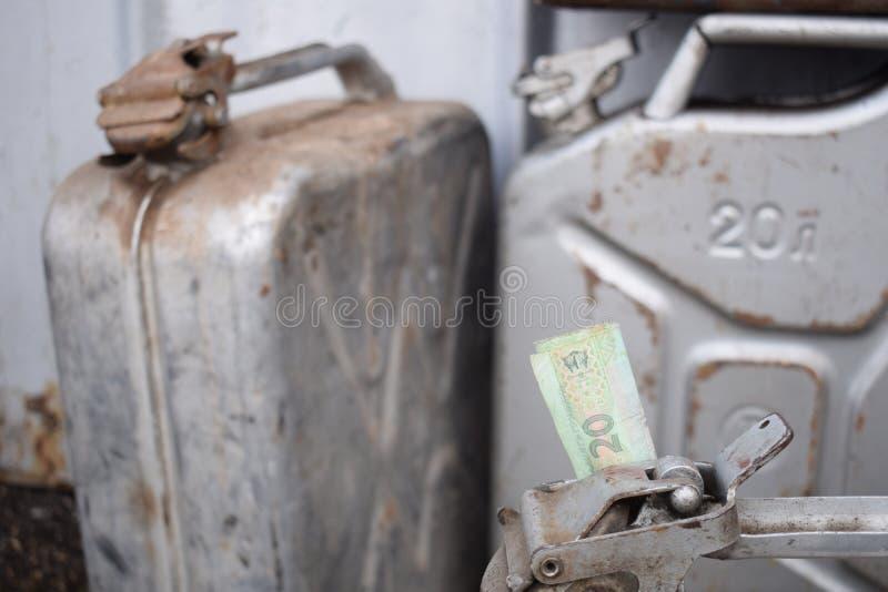 Tambor do metal e dinheiro ucraniano, o conceito do custo da gasolina, diesel, gás Reenchendo o carro 20 litros e cédula 20 imagem de stock