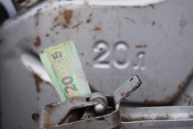 Tambor do metal e dinheiro ucraniano, o conceito do custo da gasolina, diesel, gás Reenchendo o carro 20 litros e cédula 20 imagens de stock royalty free