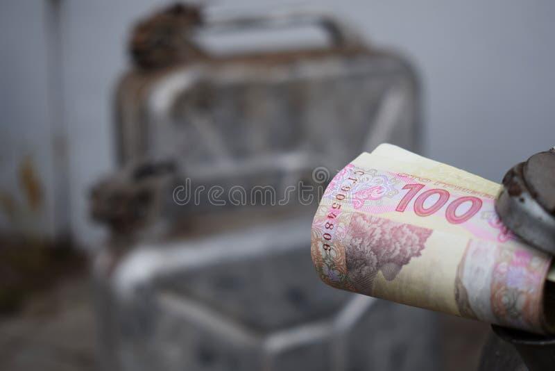 Tambor do metal e dinheiro ucraniano, o conceito do custo da gasolina, diesel, gás Reenchendo o carro Rolo das cédulas 100 foto de stock