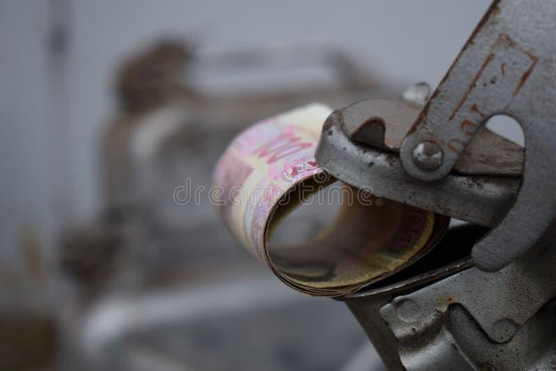 Tambor do metal e dinheiro ucraniano, o conceito do custo da gasolina, diesel, gás Reenchendo o carro Rolo das cédulas 100 imagens de stock