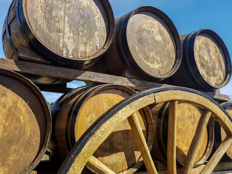Tambores com vinho na roda de vagão de madeira retro imagens de stock royalty free