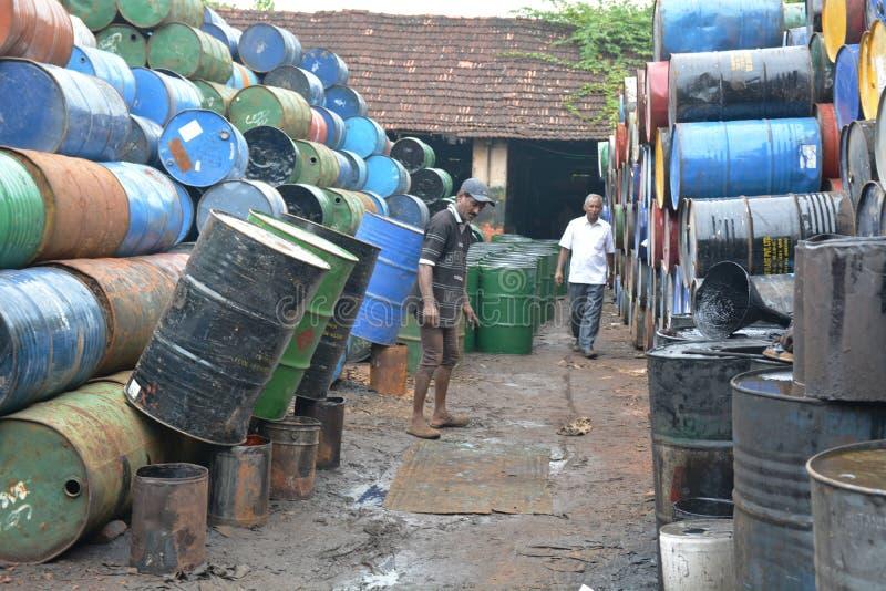 Tambores de óleo indianos da limpeza dos trabalhadores foto de stock