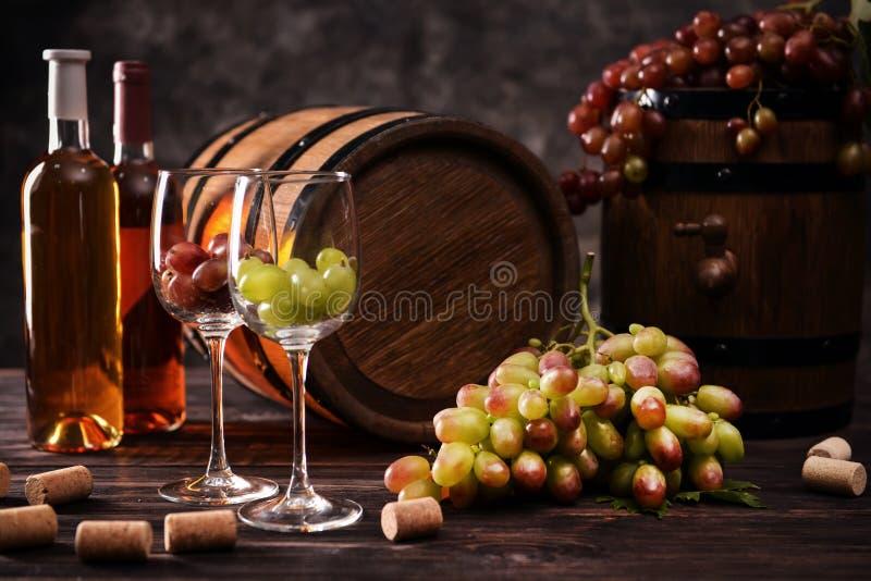Tambores de madeira com uvas, vidros e as garrafas maduros do vinho na tabela foto de stock royalty free