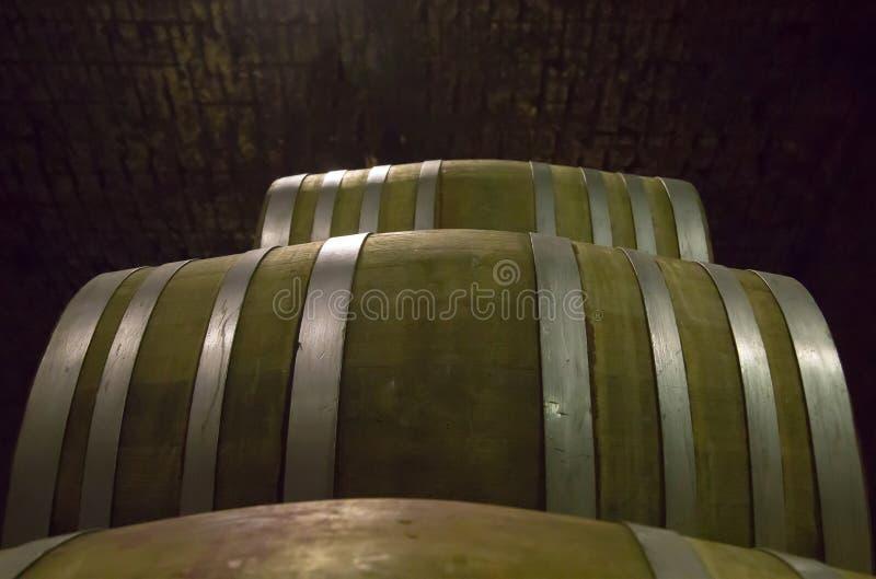 Tambores de vinho da madeira dura prendida com correias com as aros de aço empilhadas imagem de stock