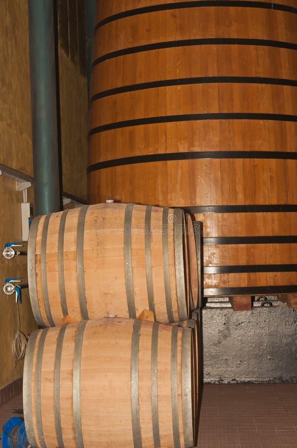 Tambores de vinho empilhados na frente de um tanque da separação da uva fotos de stock royalty free