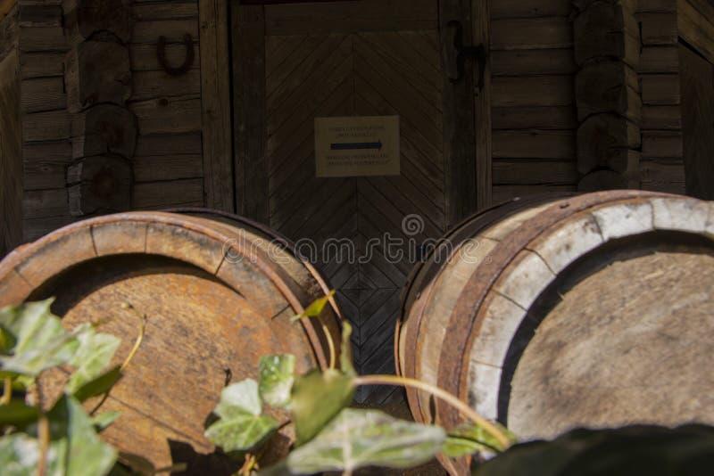 Tambores de vinho velhos no fundo de madeira da porta com a esfera oxidada do tambor fora fotografia de stock royalty free