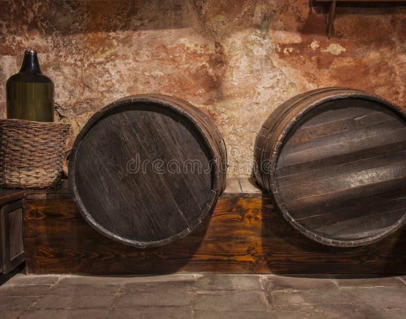 Tambores e garrafa do barril de vinho empilhados na adega velha imagens de stock royalty free