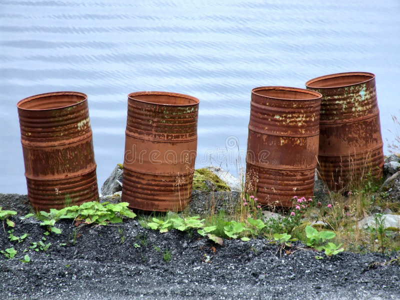 Tambores waste oxidados velhos pelo mar fotografia de stock