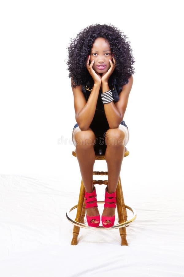 Tamborete de assento da menina adolescente afro-americano magro foto de stock