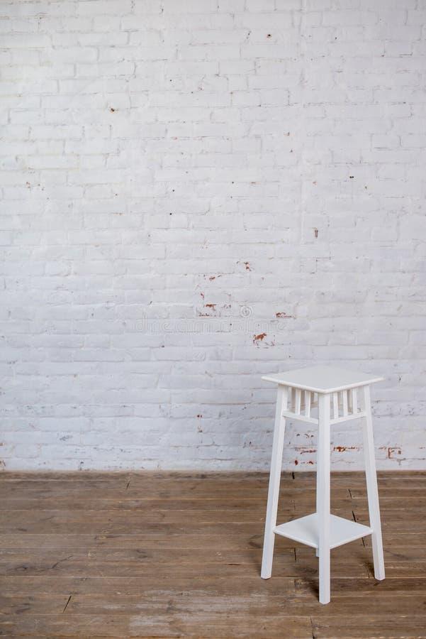Tamborete de barra branco no assoalho de madeira contra a parede de tijolo branca foto de stock