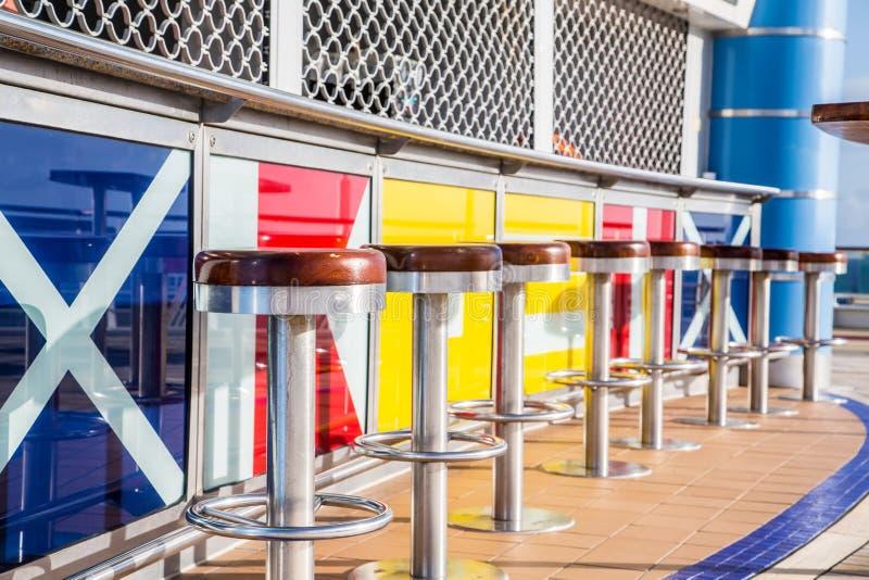 Tamboretes de barra na plataforma colorida do navio de cruzeiros imagens de stock