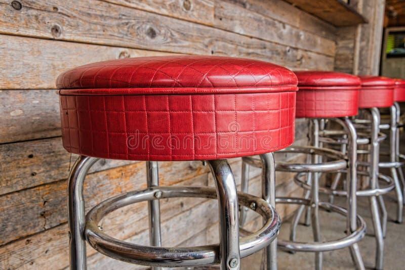 Tamboretes vermelhos brilhantes do jantar do vintage do ósmio da fileira imagens de stock