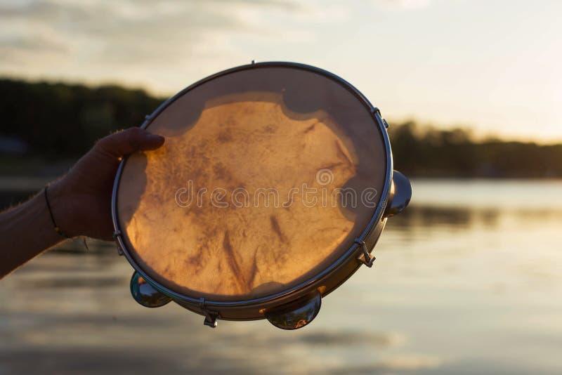 Tamburino o pandeiro dello strumento musicale su un fondo del cielo al tramonto immagine stock libera da diritti