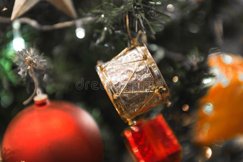 Tamburo d'argento bianco di Natale che appende su un bello albero di Chrismas circondato dalla palla shinning rossa fotografia stock