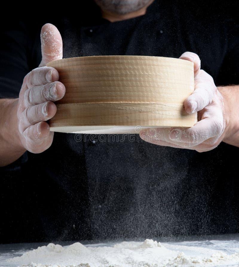 Tamis en bois rond dans des mains masculines photos stock