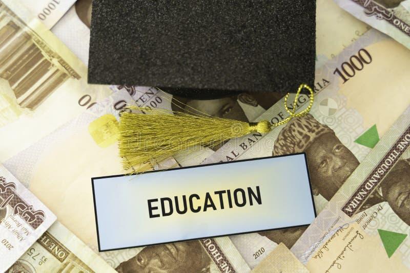 Tamp?o acad?mico do barrete da universidade em notas nigerianas do naira foto de stock