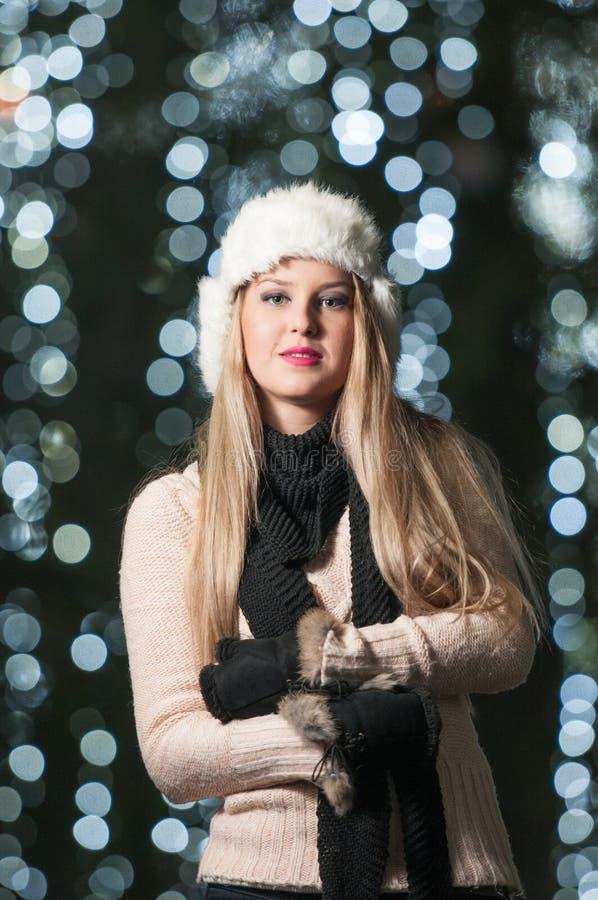 Tampão branco vestindo da pele da senhora elegante e silencioso preto exteriores no cenário do Xmas com luzes azuis no fundo. Retr foto de stock