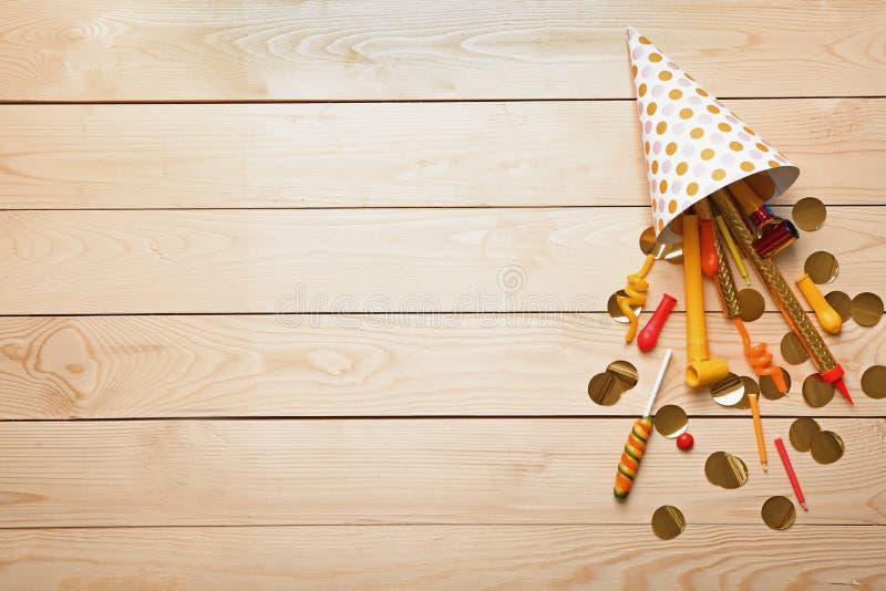 Tampão com artigos da festa de anos no fundo de madeira fotografia de stock