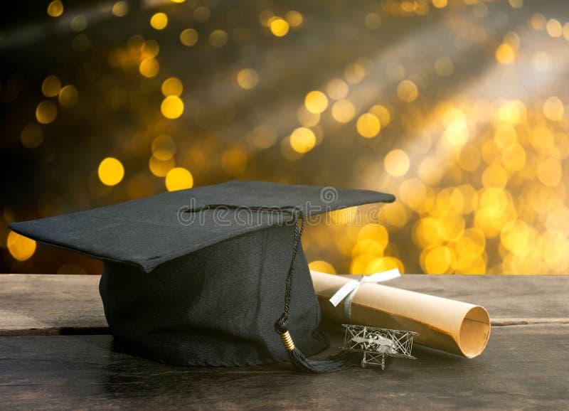 tampão da graduação, chapéu com papel do grau na tabela de madeira, li abstrato fotos de stock