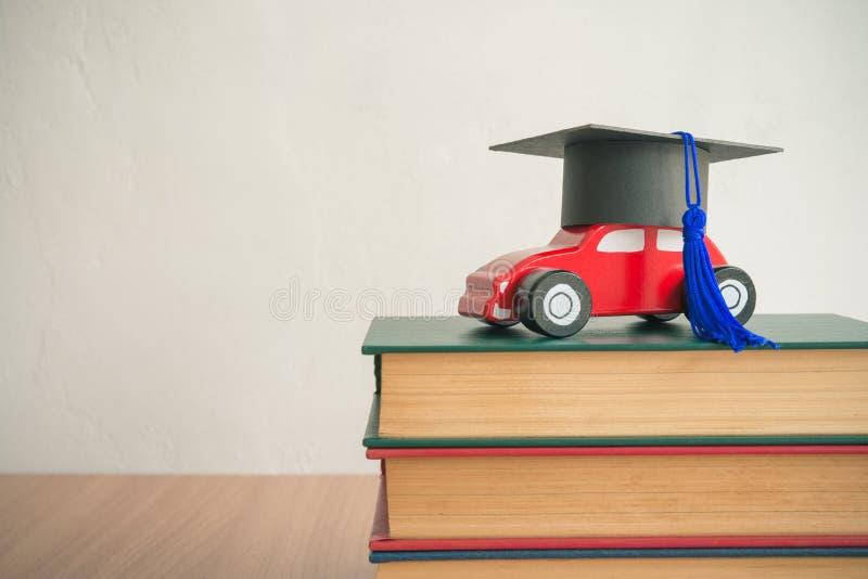 Tampão da graduação no carro de madeira sobre a pilha dos livros em wal branco imagens de stock royalty free