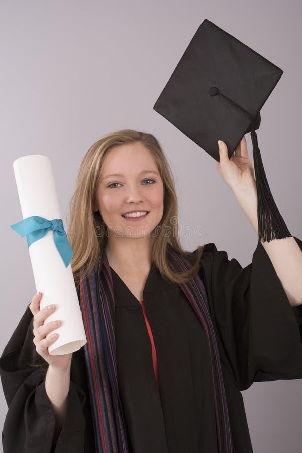 Tampão e diploma guardando graduados da universidade fotos de stock