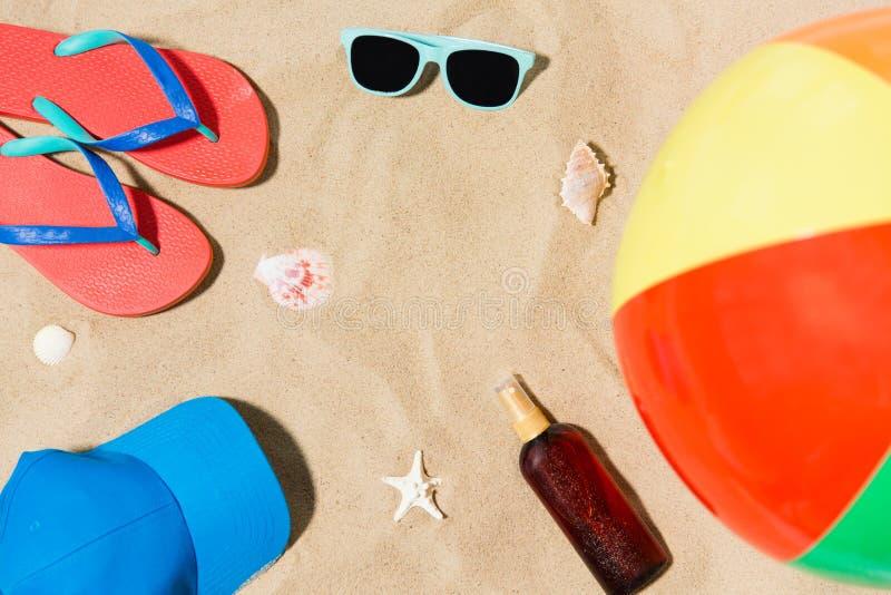 Tampão, falhanços de aleta e máscaras e bola de praia na areia foto de stock royalty free