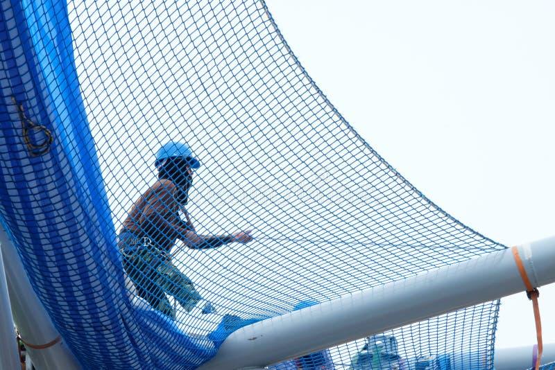 Tampão masculino do capacete do desgaste do trabalhador que puxa a rede para cobrir o telhado da construção, Banguecoque: 6 de ag imagens de stock royalty free