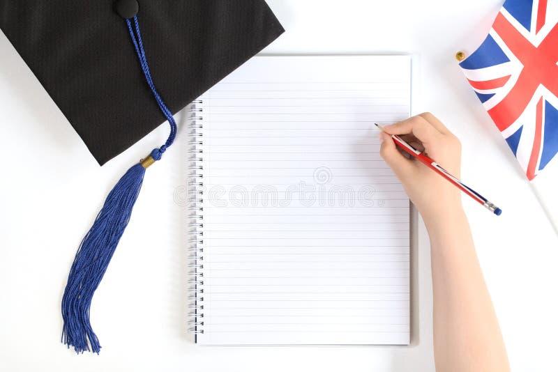 Tampão preto da graduação com caderno foto de stock royalty free