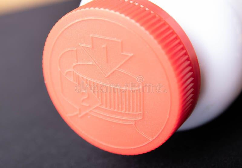 Tampão vermelho em uma garrafa branca com uma descrição de como abri-la imagens de stock