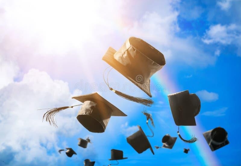 Tampões da graduação, chapéu jogado no ar com Abs do céu azul do raio do sol imagem de stock royalty free